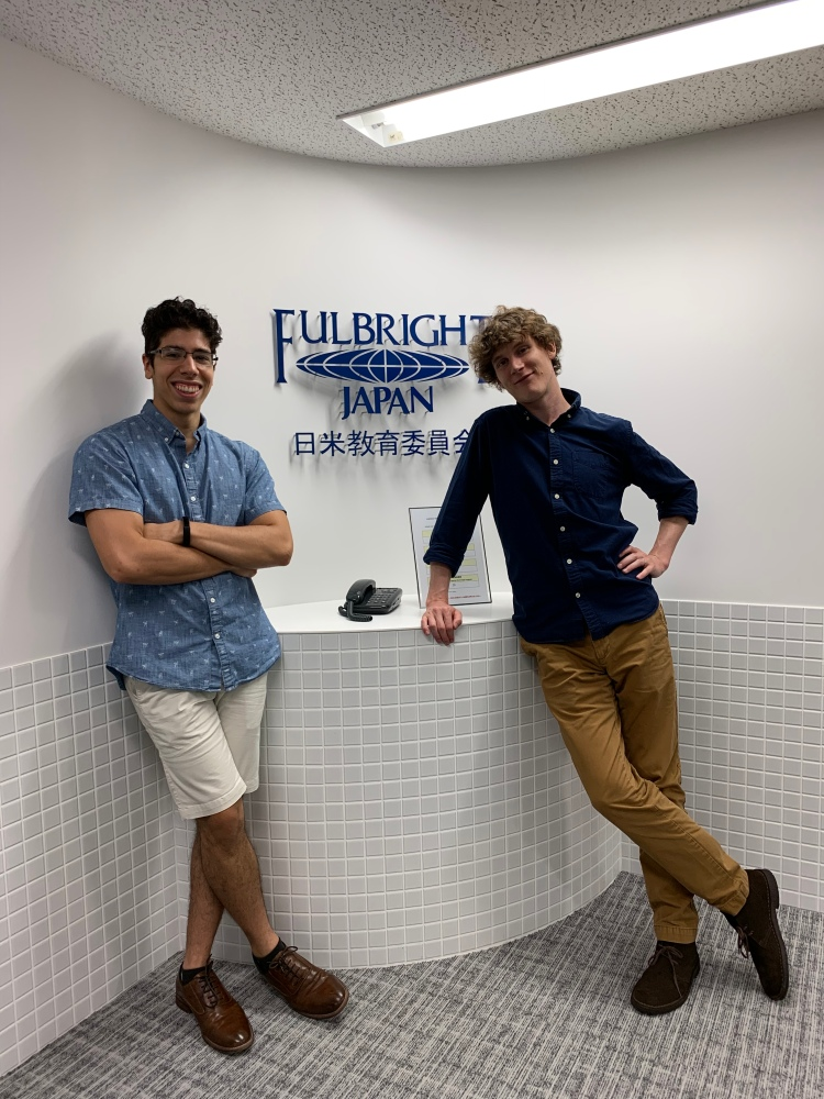 "Fellow Stanford Fulbrighters! Pictured: Me on the left, crossing my arms, and Stanford PhD Candidate Kevin Niehaus on the right, leaning on the wall. We're both smiling and in front of a sign that says ""Fulbright Japan"" - we're right outside their offices."